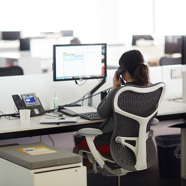 Woman sitting at her office desk while talking on the phone.