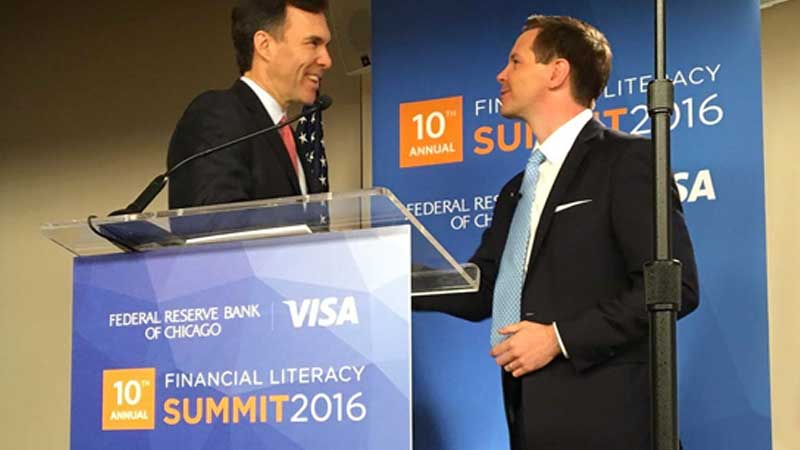 two men in suits at a podium for the financial literacy summit 2016