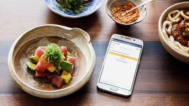 visa checkout on a mobile phone on a restaurant table with food